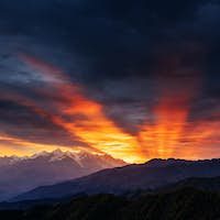 Sunset over snow-capped mountain peaks.