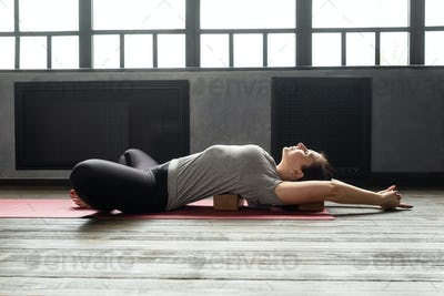 woman practicing yoga in Reclined Butterfly exercise, supta baddha konasana