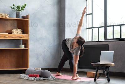 Young woman practicing yoga, doing Revolved Triangle Pose, Parivrrta Trikonasana