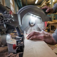 Carpenter cutting flaxboard using sliding compound mitre saw