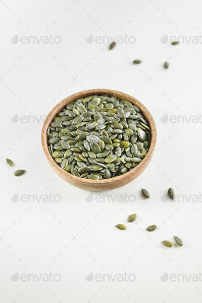 Pumpkin shelled dried seeds or pepitas in a wooden bowl