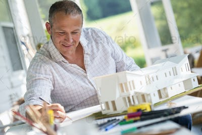 A man using a pencil drawing on a plan