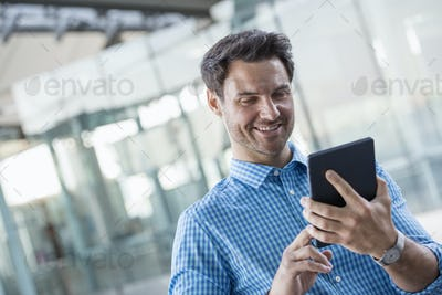 A man in a blue shirt using a digital tablet outddoors in the city