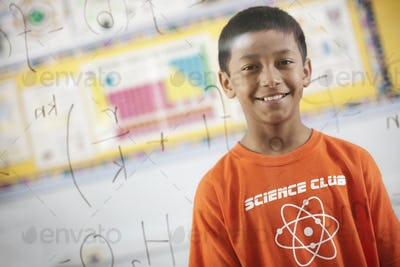 A boy looking at a board with written scientific equations and calculations.