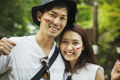 Two young people in woodland, with Japanese flags painted on their cheeks