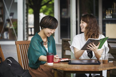 Two women at table in a street cafe, holding digital tablet, smiling.