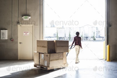 A female warehouse worker moving products with a pallet jack, to a loading door