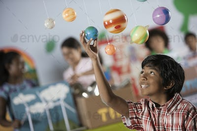 A boy looking up at a display of the planets, a presentation of the planetary system.