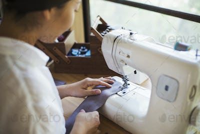 Close up of woman sitting at a sewing machine, sewing grey strip of fabric.