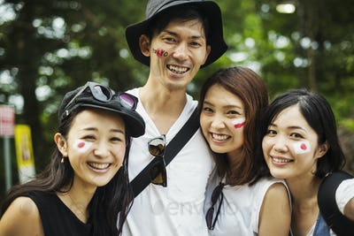 Four young people outdoors, faces painted with Japanese flags