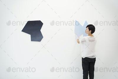 Woman with  short black hair wearing white shirt hanging modern paintings