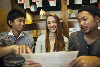 Woman and two men in a restaurant looking at the menu.