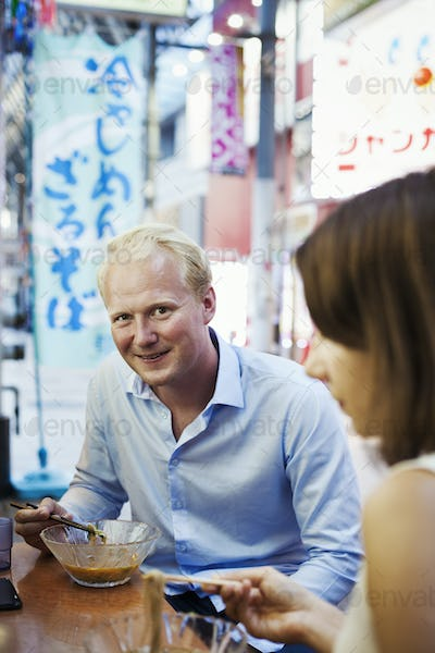 Young man and woman sitting at a table in a restaurant in Japan