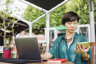 Woman sitting with a laptop at table in a cafe, with digital tablet.