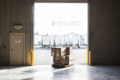 Products in boxes at a loading dock door in a distribution warehouse.