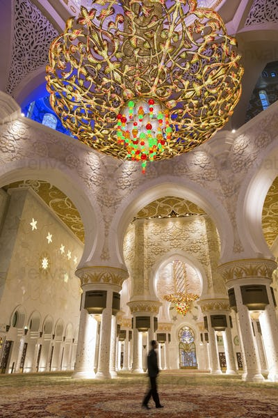Man standing underneath white and golden dome of Sheikh Zayed Mosque