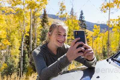 13 year old girl taking pictures with her smart phone, looking at autumn aspen trees