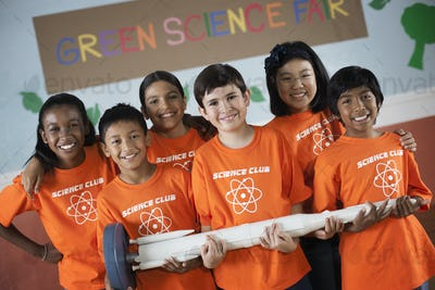Students in the Science Club standing under the sign Green Science Fair, holding a long rocket.