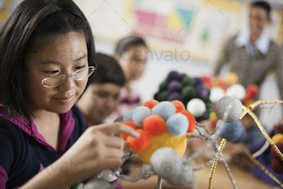 A group of students handling round shapes, making scientific models, molecular structures.