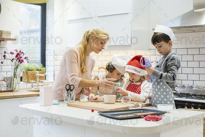 A woman and three children working together, making a gingerbread house, and icing the gingerbread.