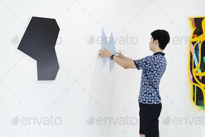 Man in art gallery, hanging modern painting on white wall.