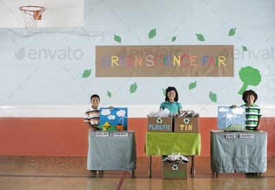 Three students standing by their project displays at a Green Science Fair event.