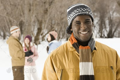 Four people outdors in hats, coats and scarves.