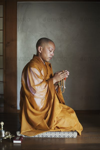 Buddhist monk in a golden robe worshipping