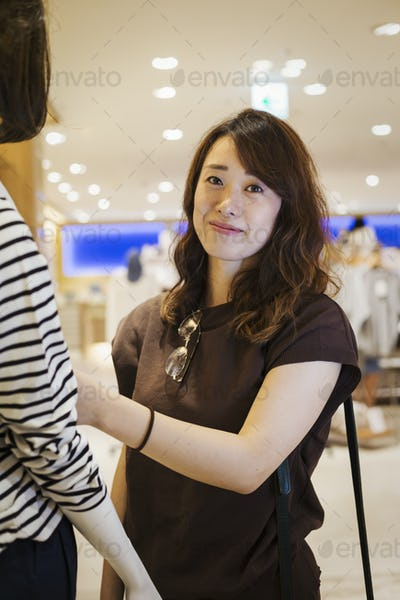 Woman standing indoors, looking at clothing in a shop, smiling at camera.