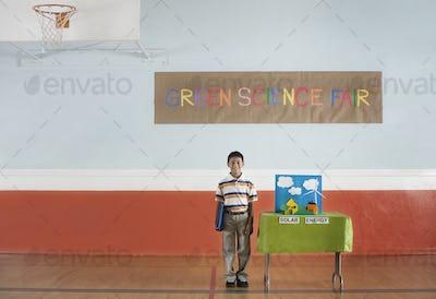 A boy standing under a Green Science Fair sign beside a Solar Power presentation.