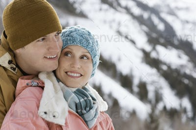 A couple hugging each other, a man and woman in the snowy mountains.