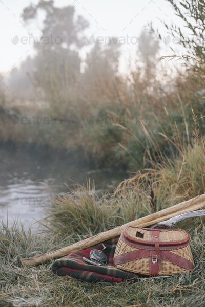 A fishing creel and blanket on the riverbank with two light rods.
