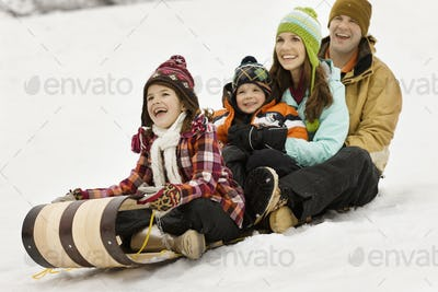 A family of two adults and two children sitting on sledges on the snow.