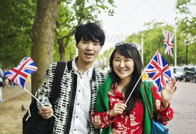 Smiling man and woman holding small Union Jack flags, looking at camera.
