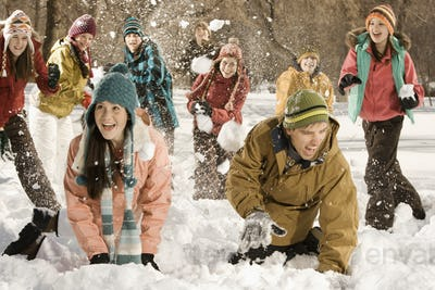 A group of children and young people having a snowball fight.