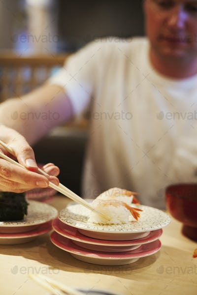 Man sitting at table in a restaurant, using chopsticks eating sushi