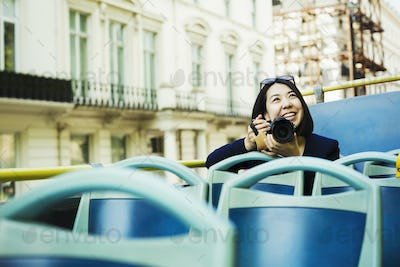 Smiling woman with camera on an open topped bus