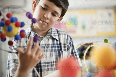A boy examining a molecular structure in a science lesson.