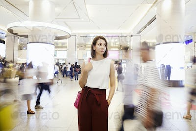 Young woman in shopping mall, blurred motion of passers by.