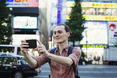 A young man on the street using his smart phone taking photographs.