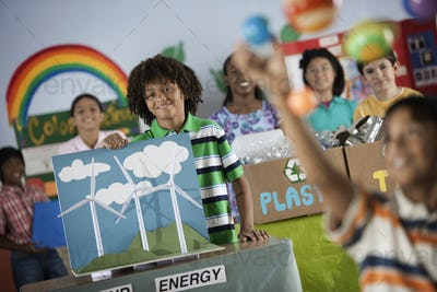 A class of children at a Green Science Fair event, with presentations on solar power and recycling.