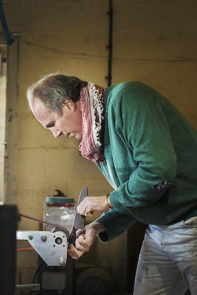 A craftsman in a knifemakers workshop