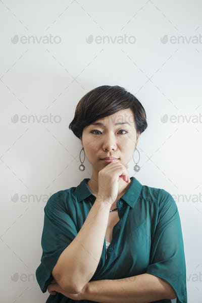 Woman standing in art gallery, hand on chin, looking at camera.