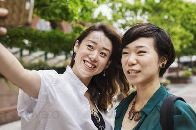 Two women outdoors, taking picture with mobile phone, smiling.