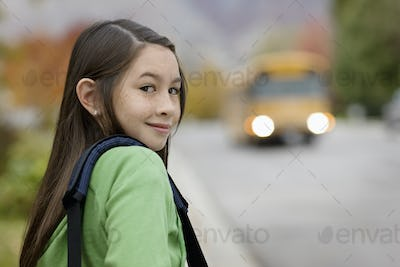 A young girl on the sidewalk, and a yellow school bus with headlights approaching.