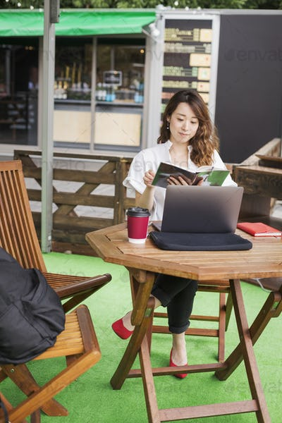 Woman sitting in front of laptop at table in a street cafe, working.