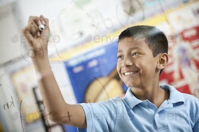 A boy writing scientific equations on a clear perspex board with a felt tip pen.