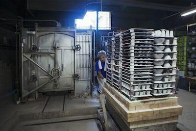 Interior view of Japanese porcelain workshop, man preparing pottery for kiln.
