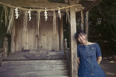 Young woman with shimenawa ropes at Shinto Sakurai Shrine