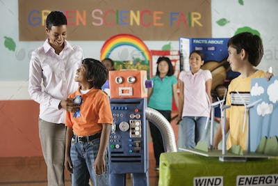 A group of students and a teacher awarding a prize to a boy standing beside a robot model.